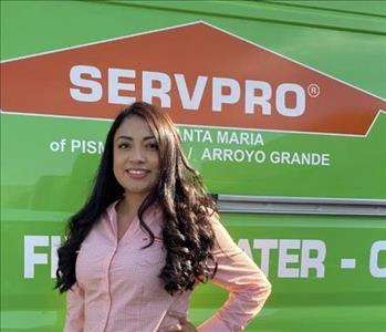 Female smiling with light orange shirt, green SERVPRO van in background